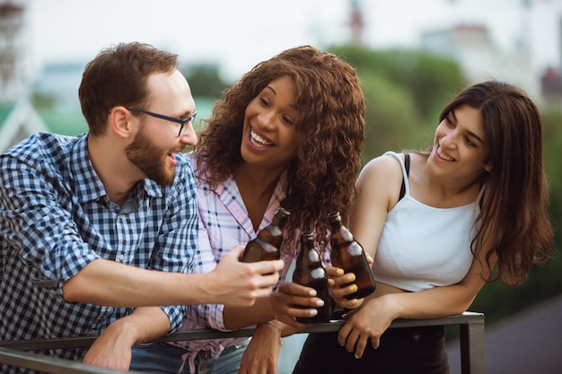 Group of happy friends having beer party in summer day.