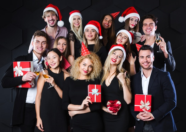 クリスマスと新年のコンセプトを楽しんでいる幸せな友達をグループ化する