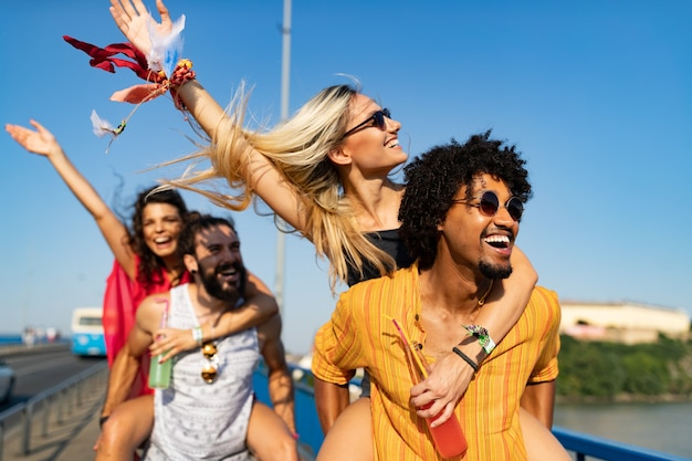 Group of happy friends having fun time at music festival
