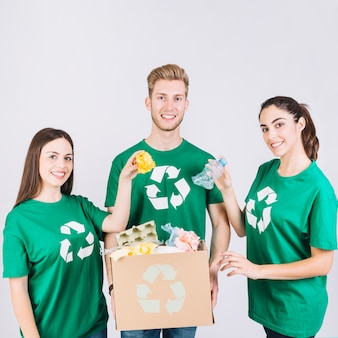 Group of happy friends holding cardboard box with recycle items