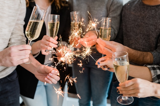 Group of happy friends holding flutes of sparkling champagne and burning bengal lights while enjoying party