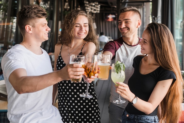 Group of happy friends holding set of drinks