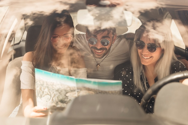 Group of happy friends looking at map sitting inside the car