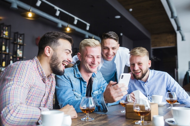 Group of happy friends looking at smartphone sitting at restaurant