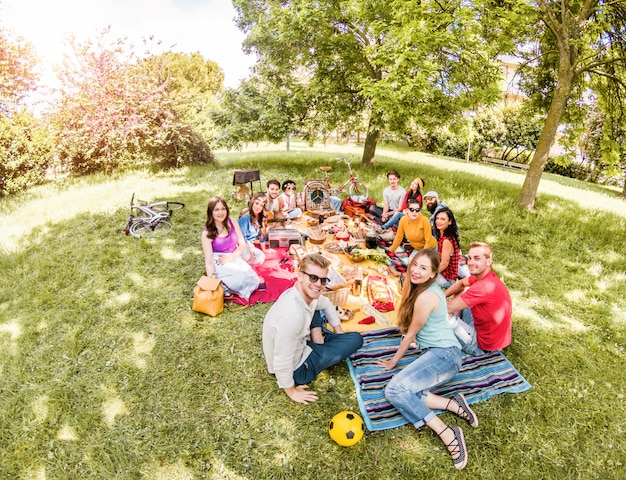 Group of happy friends making picnic on pubblic park outdoor - young people drinking wine and laughing in nature