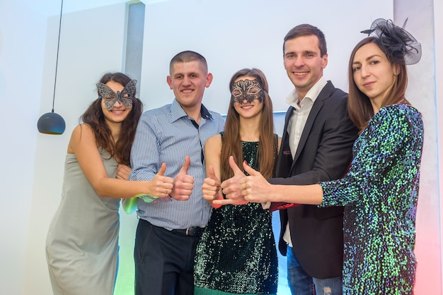 Group of happy friends in masks at new year party showing thumb up