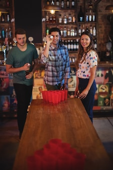 Group of happy friends playing beer pong game