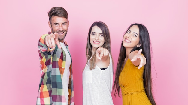 Group of happy friends pointing their fingers on pink background