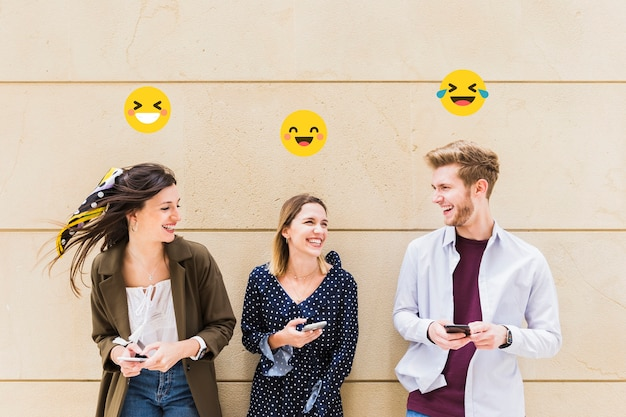 Group of happy friends sharing smiley emoji on mobile phone