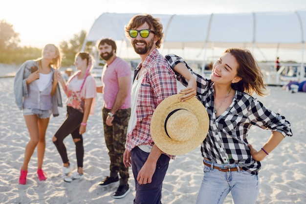 Group of happy friends spending amazing time together and walking along the sunny beach