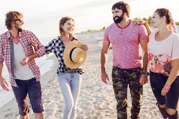 Gruppo di amici felici che trascorrono del tempo insieme e camminano lungo la spiaggia assolata