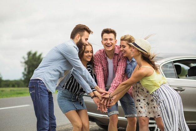 Group of happy friends standing on road putting hands together