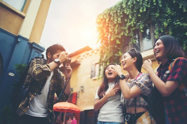 Group of happy friends taking selfies together in urban scene