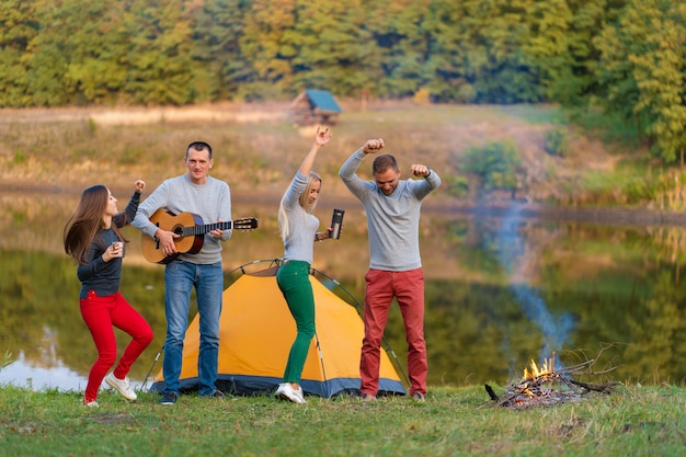 Group of happy friends with guitar, having fun outdoor, dancing and jumping near the lake in the park background the beautiful sky. camping fun