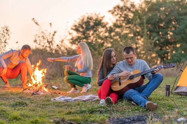Group of happy friends with guitar, having fun outdoor, near bonfire and tourist tent. camping fun happy family