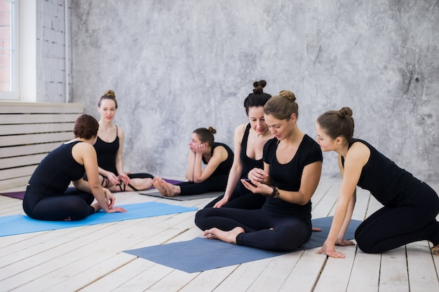Group of happy girls in fitness class at the break looking at smartphone