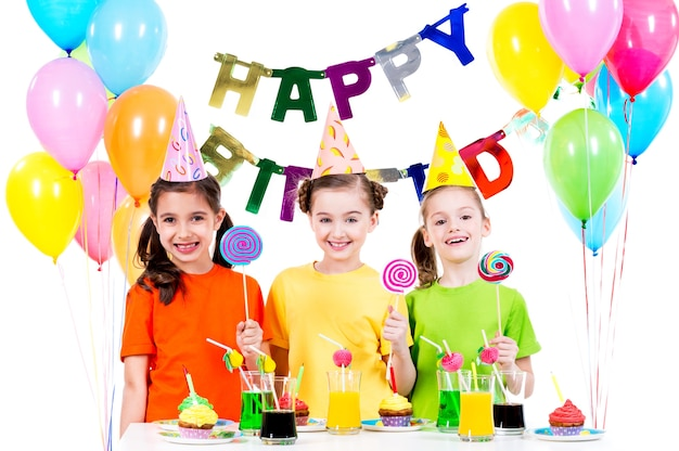 Gruppo di ragazze felici con caramelle colorate divertendosi alla festa di compleanno - isolato su un bianco