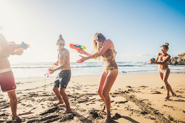 Group of happy and joyful young people having fun together in friendshp with a battle of waterguns at the beach during summer vacation