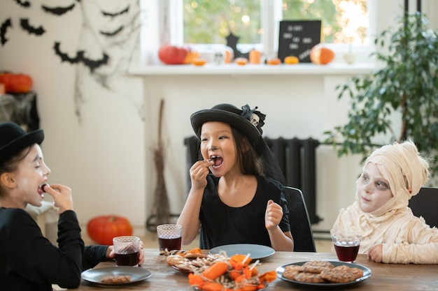 Group of happy kids in halloween costumes sitting at table in decorated living room and eating cookies and candies at tea party
