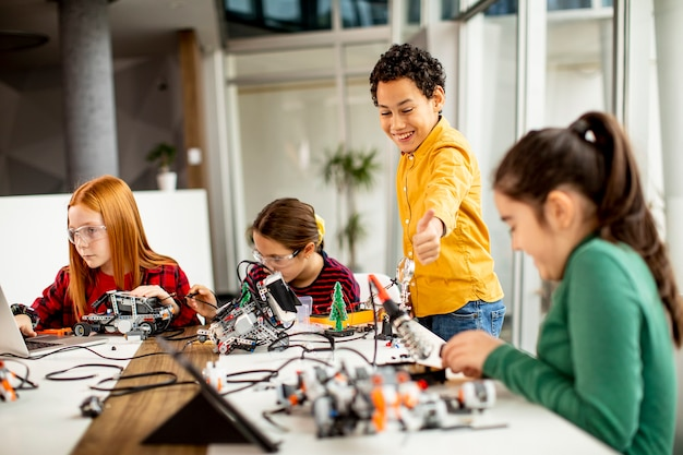 Group of happy kids programming electric toys and robots at robotics classroom