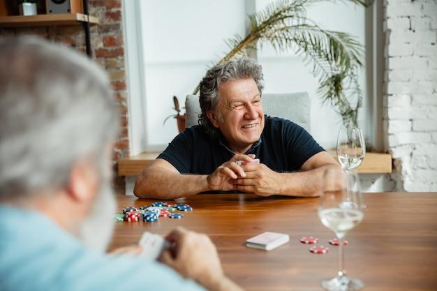 Gruppo di amici maturi felici giocando a carte e bevendo vino