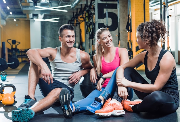 Group of happy people sitting on floor after workout