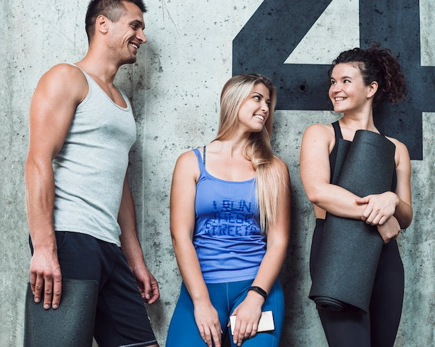 Group of happy people standing against wall in gym