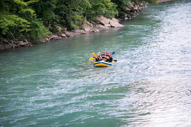 Group of happy people with guide whitewater rafting and rowing on river.