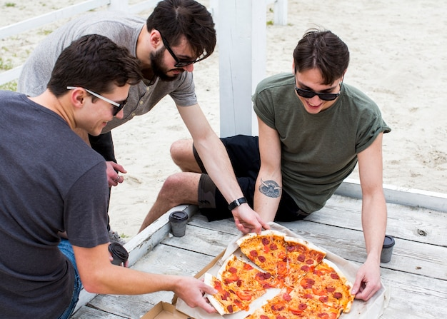 Group of happy people with pizza on rest