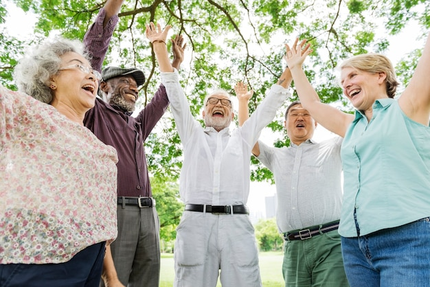 Group of happy retired senior friends  in the park cheering