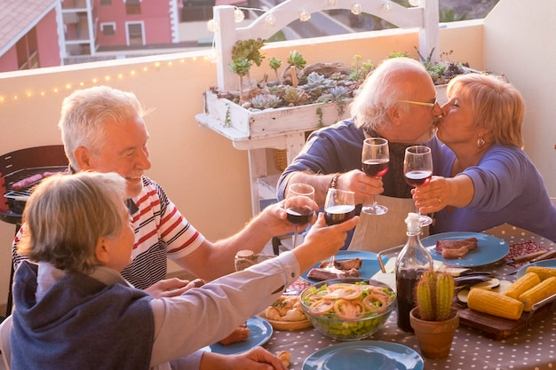 Group of happy senior old people have fun together during lunch or dinner at home in outdoor terrace