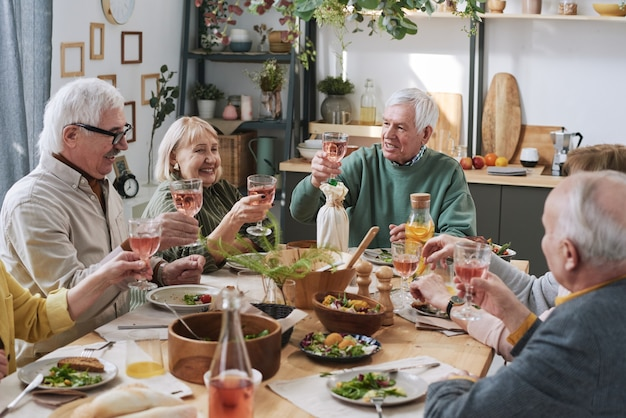 Group of happy senior people sitting at the table with glasses of red wine and having dinner at home