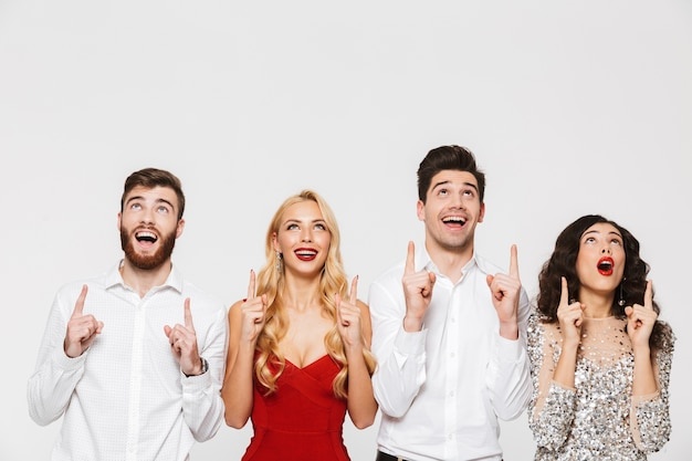 Group of happy smart dressed friends standing isolated over white, celebrating new year, pointing fingers up