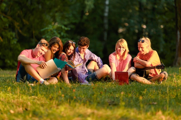Group of happy students with books in the park on a sunny day