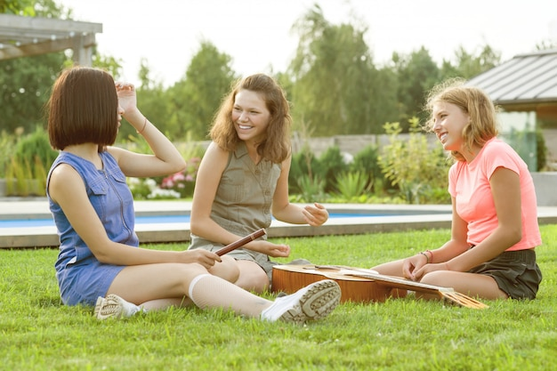 Group of happy teenage girls having fun outdoors with guitar