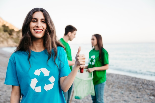 Group of happy volunteers collecting trash at the beach