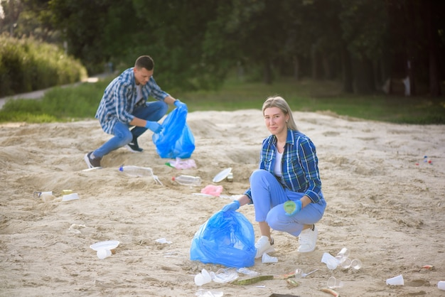 Group of happy volunteers with garbage bags cleaning area in park