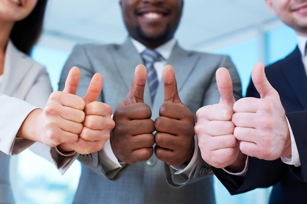 Group of happy workmates showing thumbs up