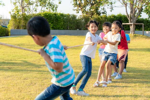 Group of happy young asian children playing tug of war or pull rope togerther outside in city park playground in summer day. children and recreation concept.