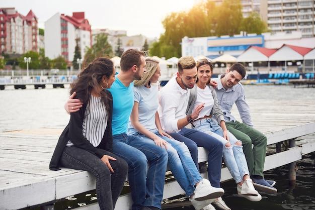 Gruppo di giovani amici felici sul molo, il piacere di giocare crea vita emotiva.