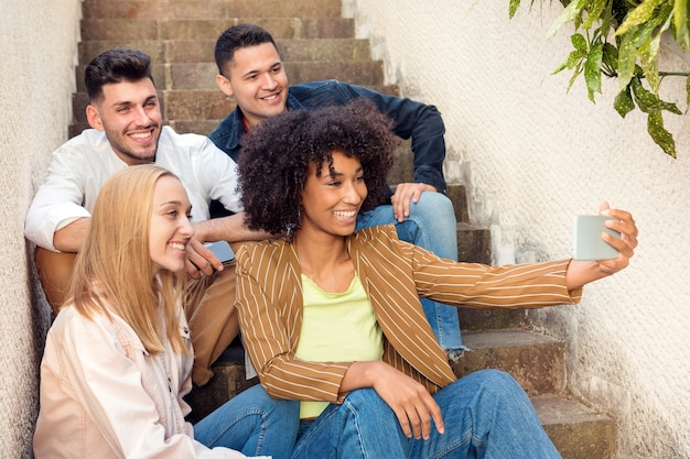 Group of happy young friends posing together on exterior steps for a selfie on a mobile phone laughing and smiling at the camera