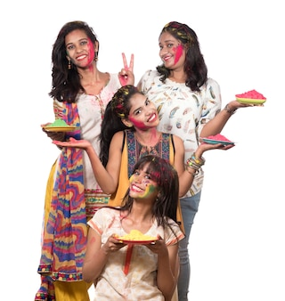Group of happy young women having fun with colorful powder at holi festival of colors