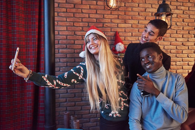 Group of ãƒâƒã'â'ãƒâ'ã'âheerful old friends communicate with each other and make a selfie . new year is coming. celebrate the new year in a cozy home atmosphere
