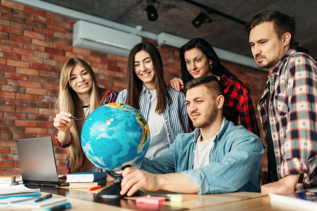 Group of highschool students looking at the globe