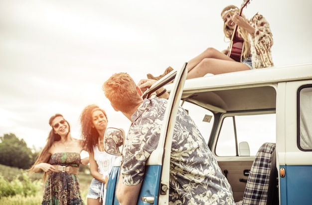 Group of hippie style friends traveling together with a vintage van