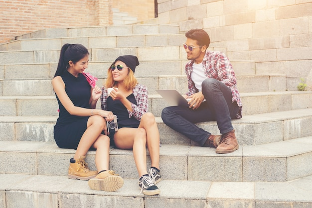 Group of hipster students sitting on a staircase talking and rel