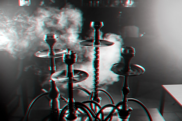 Group of hookahs in the interior of a hookah room with smoke