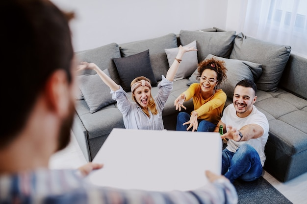 Group of hungry friends sitting on the floor and cheering