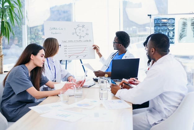 Group of ilnternatiomal doctors or interns with mentor meeting and taking notes at hospital room.