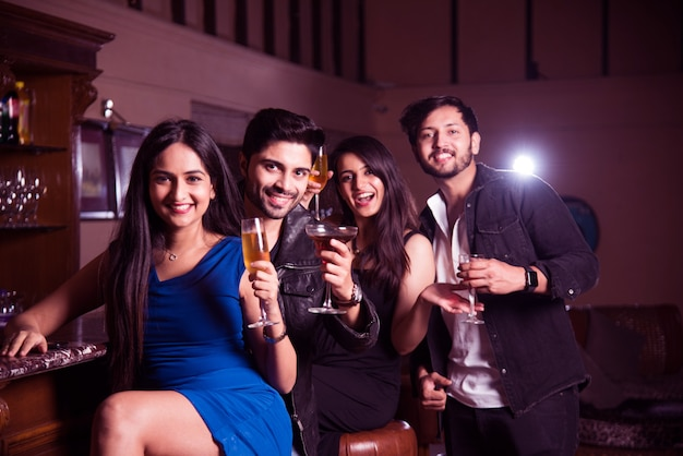Group of indian asian friends sitting at lounge bar, having drinks or cocktails, celebrating new year, birthday or success